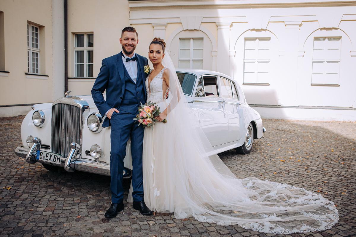 Die Braut und Bräutigam posieren vor dem Hochzeitsauto im Schloss Köpenick